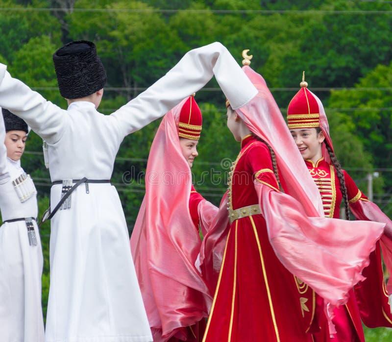 Девушки и мальчики Adyghe в национальных костюмах танцуют к черкесскому этническому фестивалю в Adygeya стоковые фото
