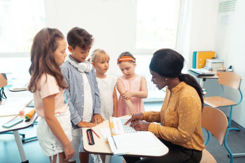 Девушки и положение мальчика около их учителя говоря им результаты теста стоковые изображения rf