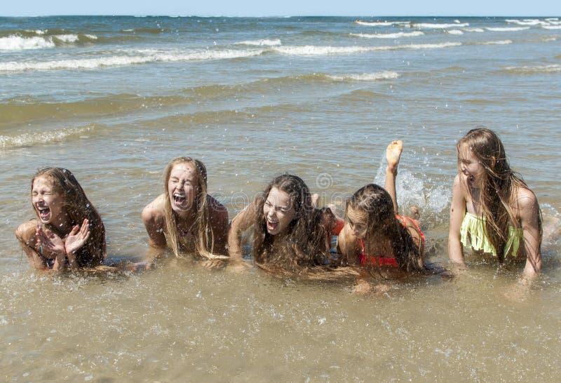Девушки лета играя в море стоковые изображения rf