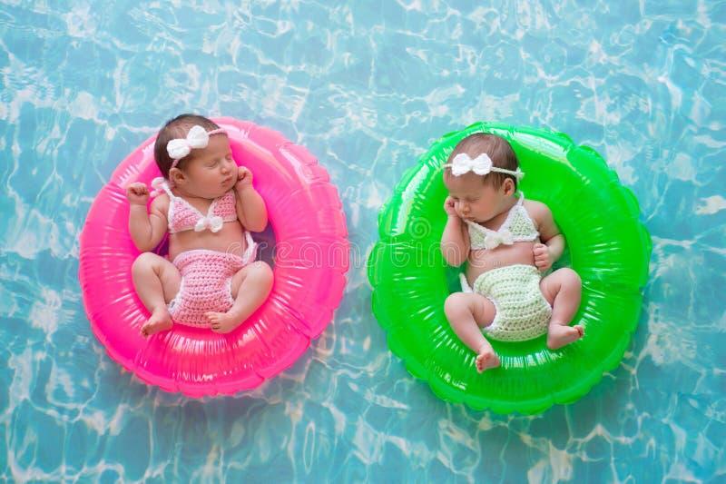 Девушки младенца двойные плавая на кольца заплыва стоковая фотография