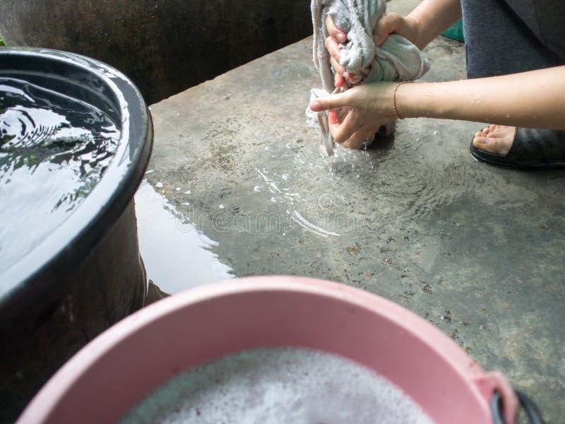 Девушки моют прачечную около дома для того чтобы убрать дом стоковое изображение