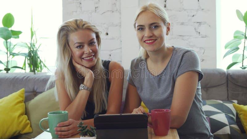 2 девушки наблюдают что-то на таблетке стоковые изображения
