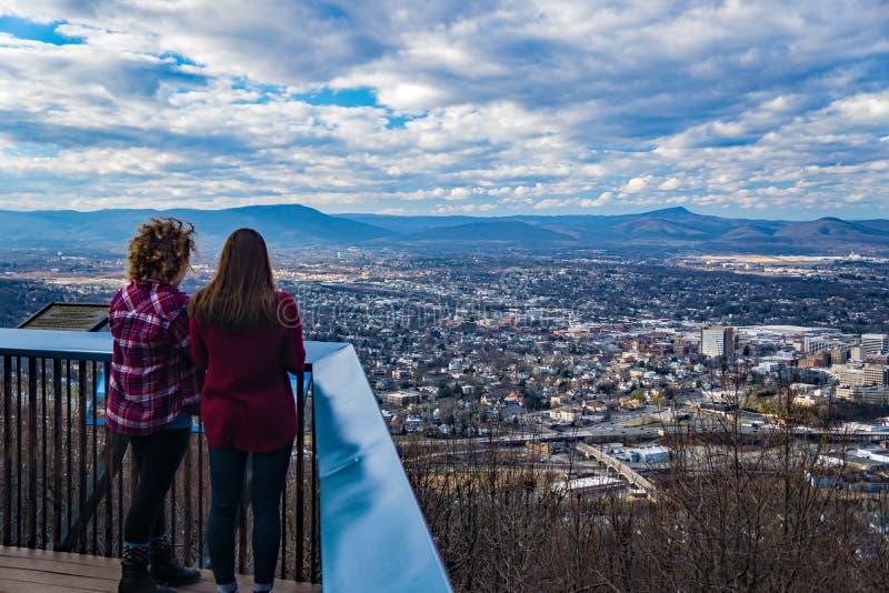 2 девушки наслаждаясь взглядом от горы мельницы обозревают стоковая фотография rf