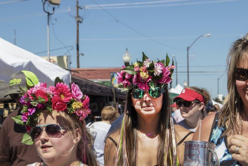Девушки на кронах цветка фестиваля нося с лентами идя в улицу среди толпы - конец-вверх и выборочное стоковое изображение rf