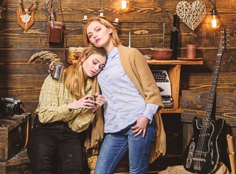 Девушки на расслабленных сторонах держат металлические кружки, наслаждаются уютом с напитками Друзья проводят душевный вечер, вну стоковая фотография rf