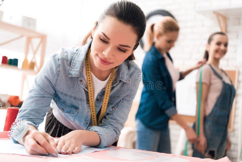 3 девушки на фабрике одежды Одно из их использует пинту для выреза стоковые изображения