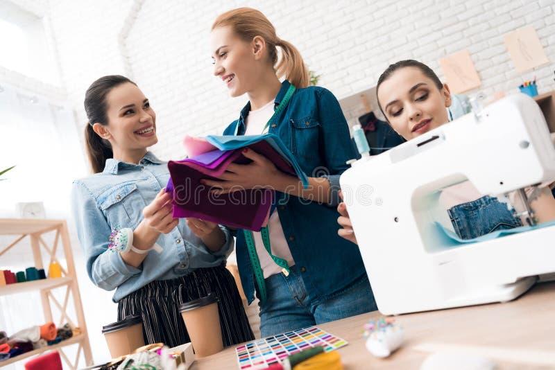 3 девушки на фабрике одежды Они выбирают ткань для нового платья стоковые фото