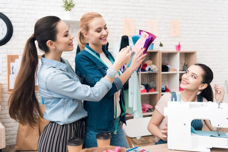 3 девушки на фабрике одежды Они выбирают ткань для нового платья стоковая фотография