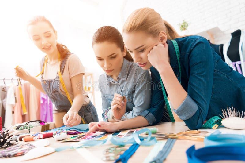 3 девушки на фабрике одежды Они выбирают цвета для нового платья стоковое изображение