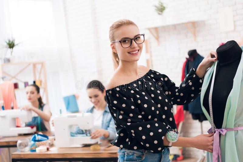 3 девушки на фабрике одежды Они сидят за швейными машинами и принимают измерения нового платья стоковое фото