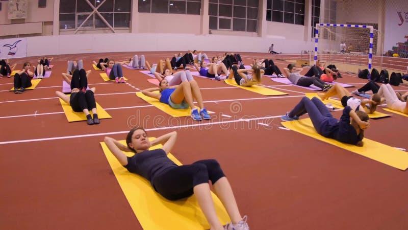 Девушки на циновках на спортзале делая тренировку стоковые изображения