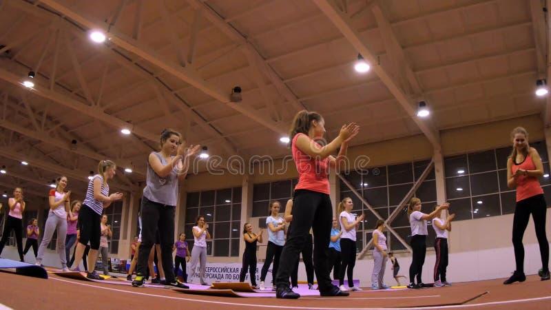 Девушки на циновках на спортзале делая тренировку стоковое фото rf