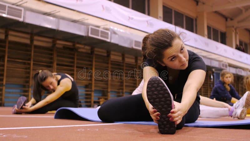 Девушки на циновках на спортзале делая тренировку стоковая фотография