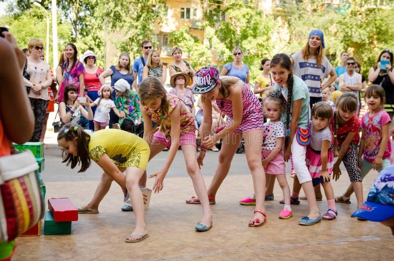 Девушки объединяются в команду играющ коробку одина другого пропуска забавной игры между их ногами на партии пирата стоковое фото