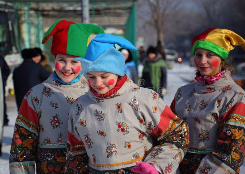 Девушки одели в традиционных русских одеждах представляют скоморохов стоковое фото rf