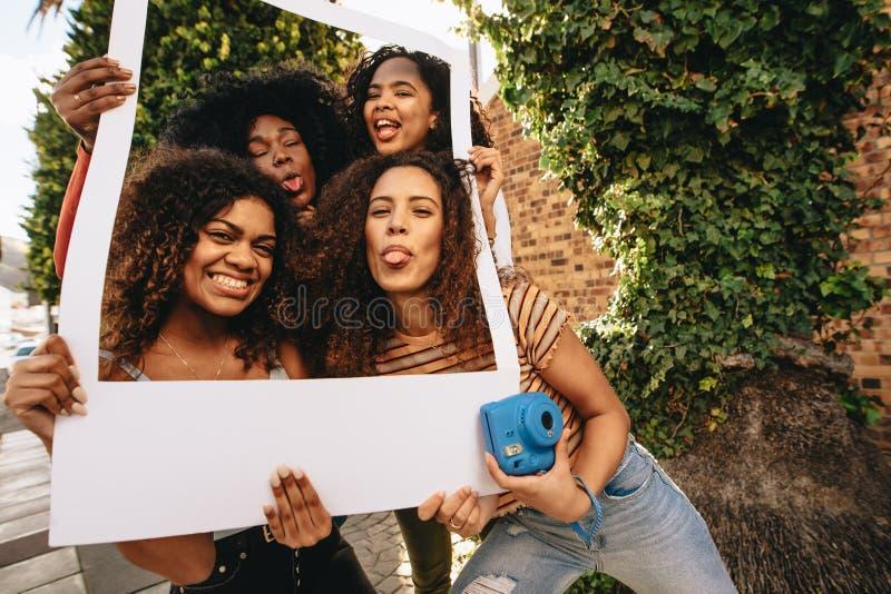 Девушки представляя с пустой картинной рамкой стоковые фото