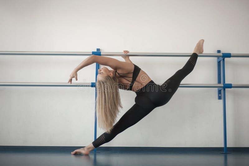 Девушки пригонки подготавливая разминку ног Нога протягивая женщину фитнеса тренировки делая подогрев, мышцы подколенного сухожил стоковое изображение