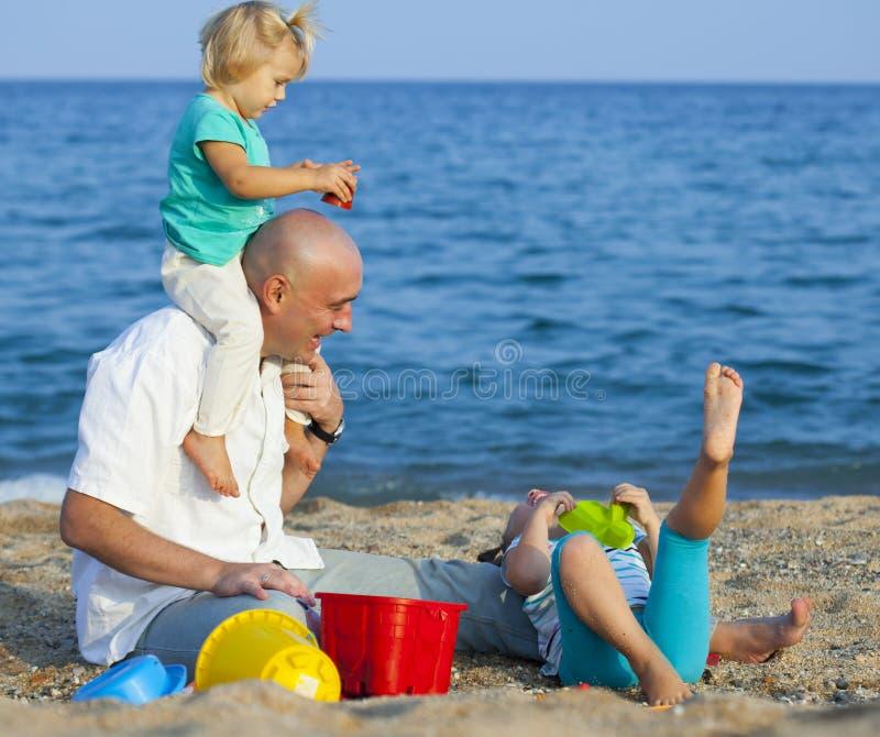 Девушки при папа играя на море стоковое изображение rf