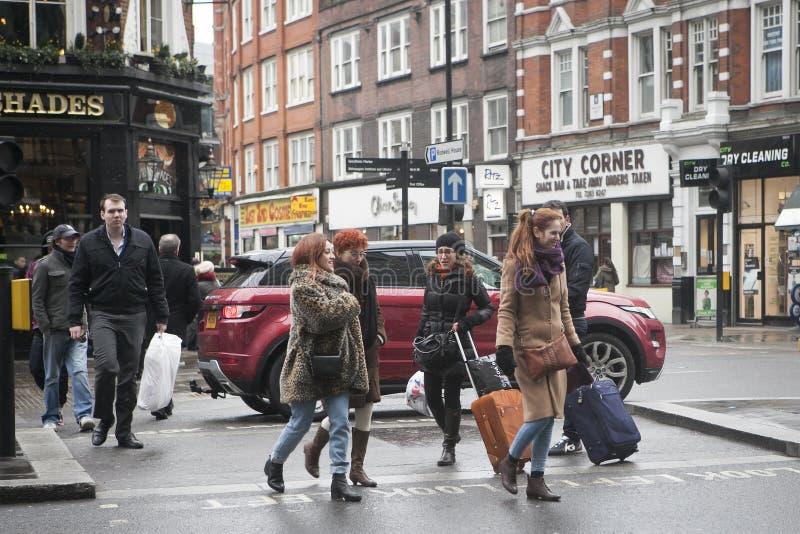Девушки при чемоданы пересекая улицу около национального выражают стоп, где вы можете принять шину идя к Stansted стоковое фото