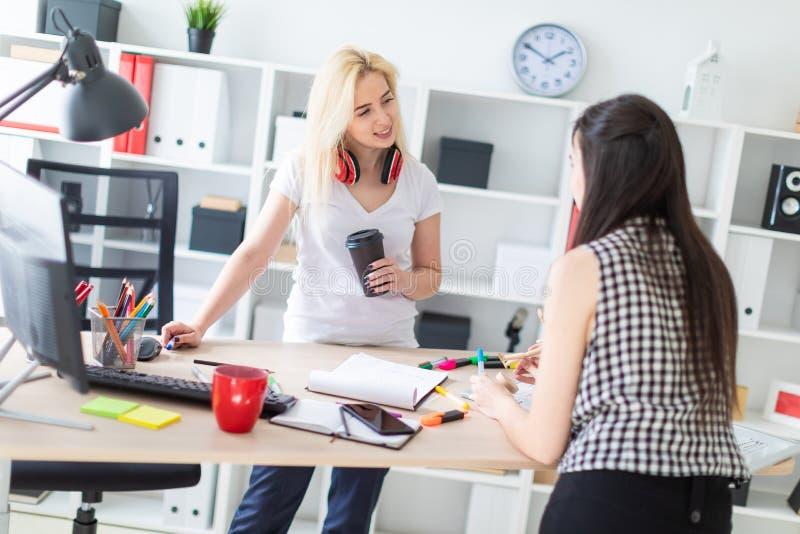 2 девушки работают в офисе Девушка держит модель человека стоковое изображение