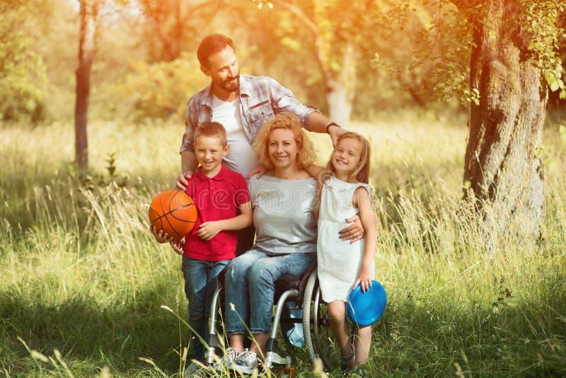 3 девушки семьи кресла камеры смотрящ сидеть re портрета мати померанцовый их там Женщина в кресло-коляске с ее семьей outdoors стоковые изображения rf