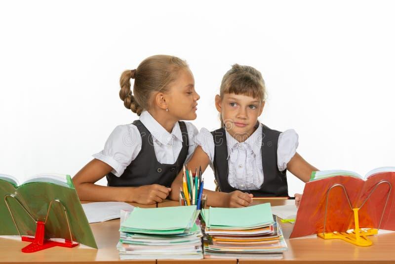 Девушки сидят на столе школы, одном шепчут к другому что-то в ухе стоковое изображение rf