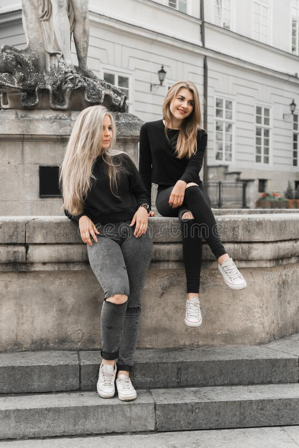 Девушки сидя на фонтане Концепция летних отпусков стоковое изображение