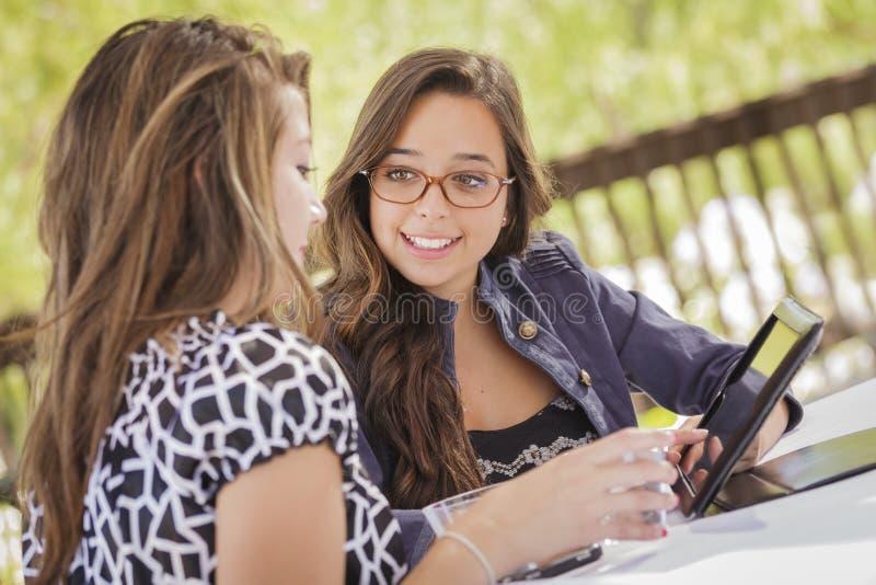 Девушки смешанной гонки работая на компьютере таблетки стоковое фото rf