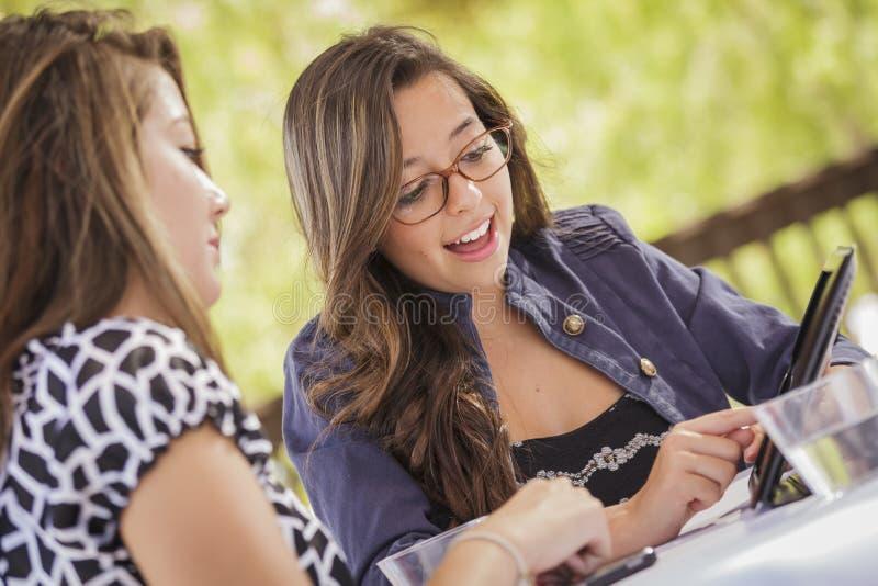 Девушки смешанной гонки работая совместно на планшете стоковая фотография rf