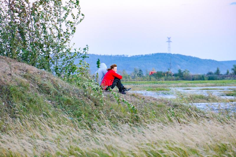 Девушки смотрят воду в поле стоковое изображение