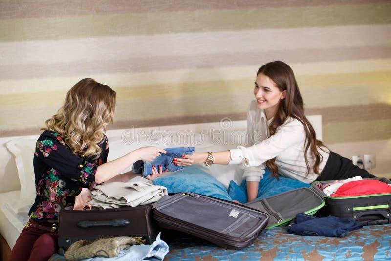 2 девушки собирают чемодан в гостиничном номере стоковое фото