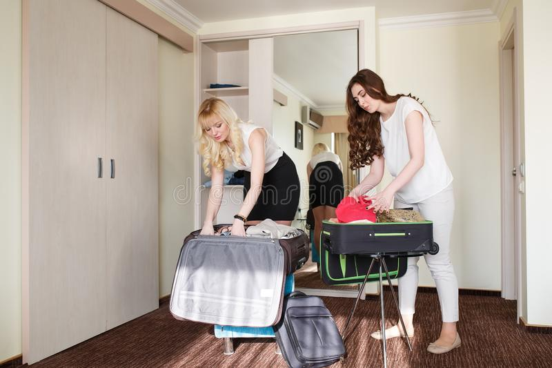2 девушки собирают чемодан в гостиничном номере стоковые изображения