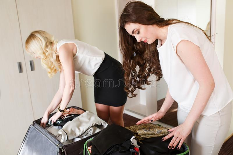 2 девушки собирают чемодан в гостиничном номере стоковое изображение rf