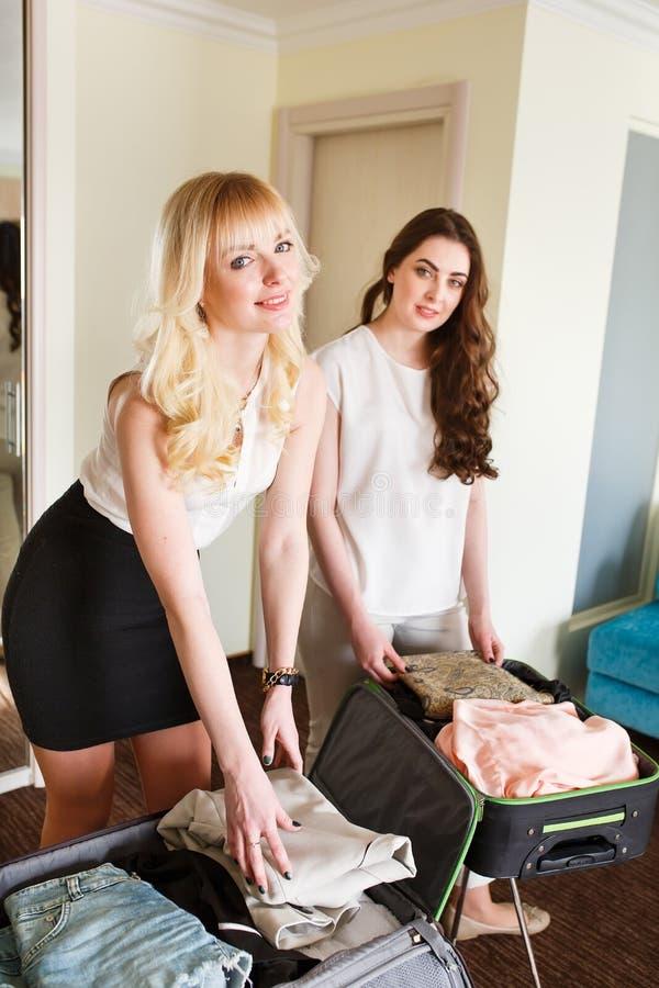 2 девушки собирают чемодан в гостиничном номере стоковые изображения rf
