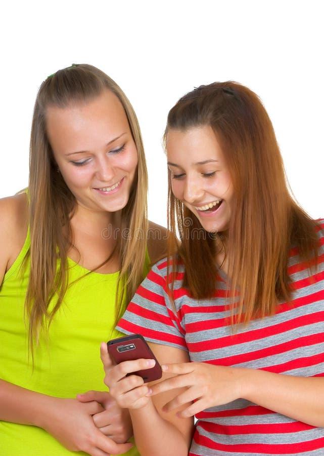 девушки сообщения знонят по телефону прочитали 2 стоковое фото