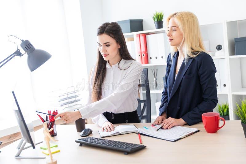 2 девушки стоят в офисе около таблицы и взгляде на мониторе стоковое фото rf