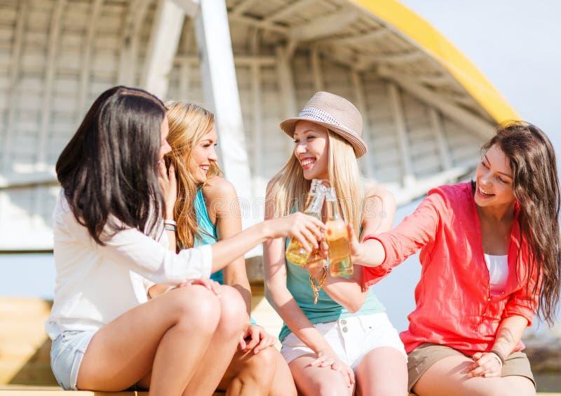 Девушки с пить на пляже стоковое фото rf