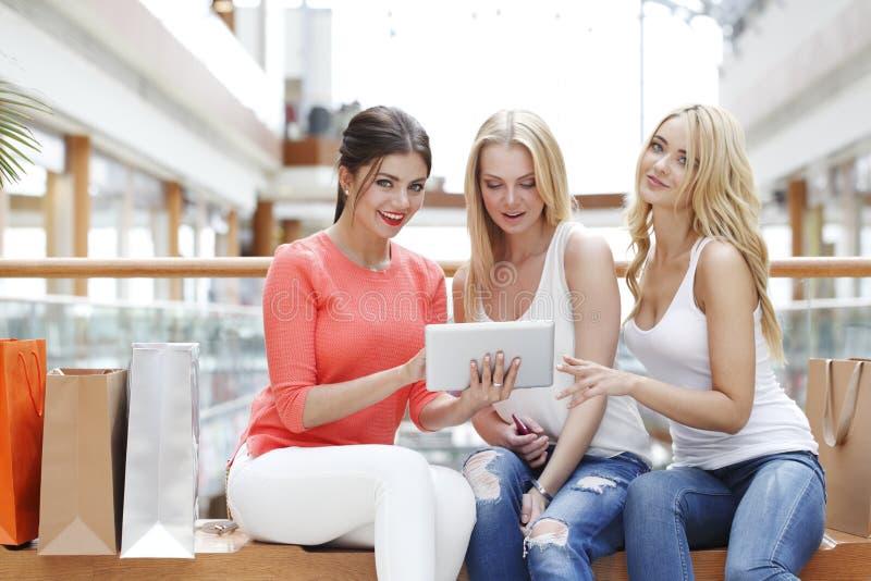 Девушки с планшетом в торговом центре стоковые фотографии rf