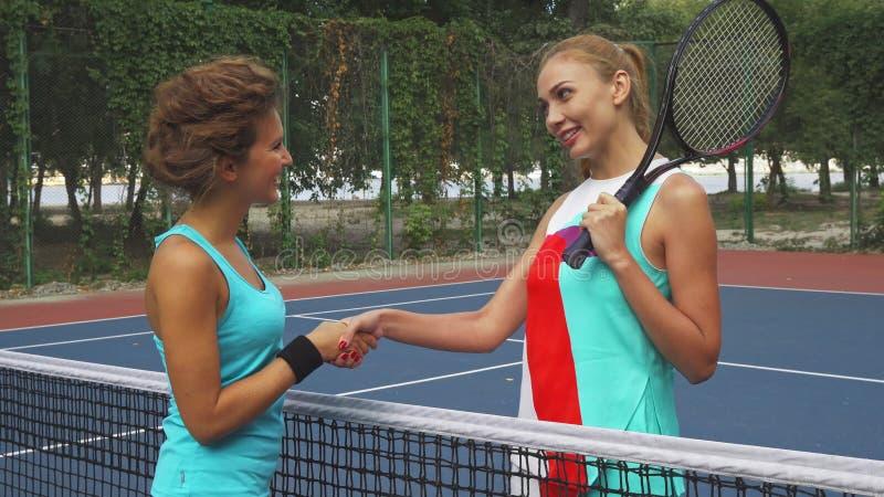 2 девушки тряся руки перед играть теннис стоковое изображение