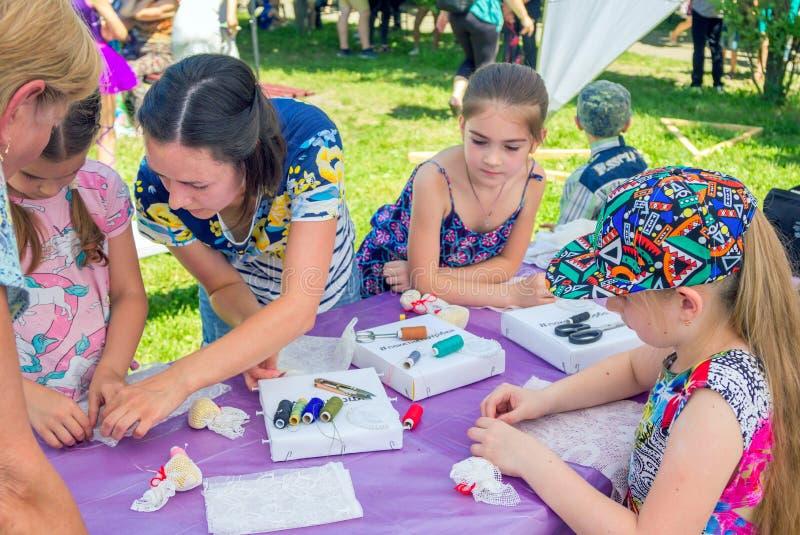 Девушки участвуя на шить мастерской outdoors стоковое фото rf