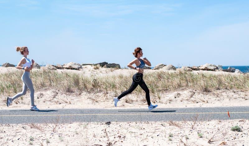Девушки фитнеса бежать на пляже стоковые изображения rf