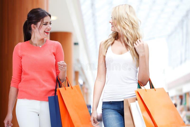 Девушки ходя по магазинам в торговом центре стоковое изображение
