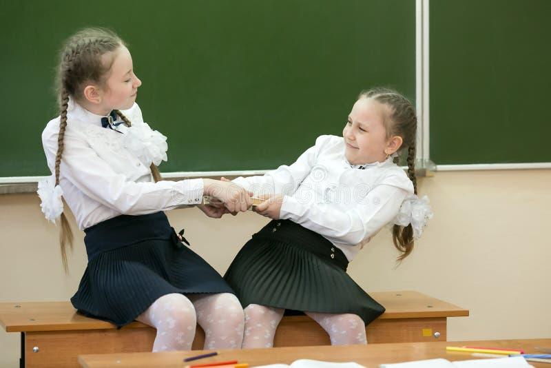Девушки школьницы принимают книгу от одина другого стоковая фотография rf