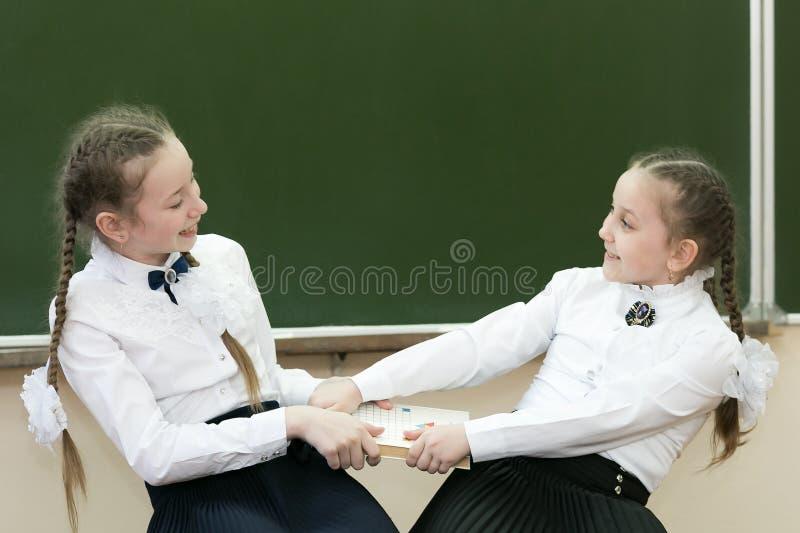 Девушки школьницы принимают книгу от одина другого стоковое изображение rf