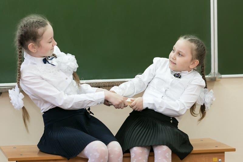 Девушки школьницы принимают книгу от одина другого стоковые изображения rf