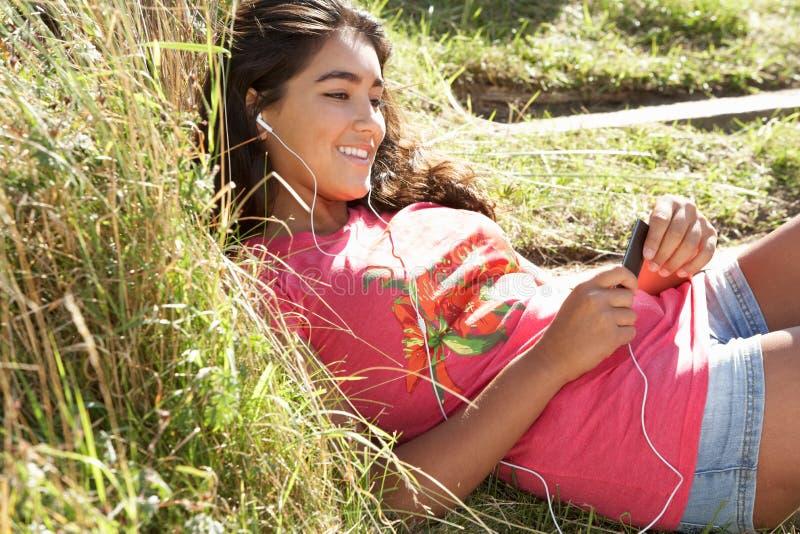 девушки mp3 использование игрока outdoors подростковое стоковые изображения