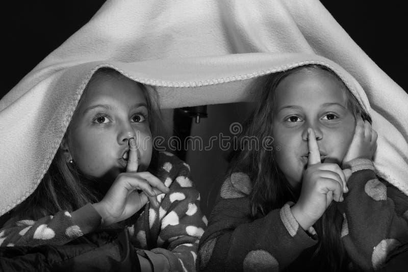 Девушки shushing с их пальцами на губах смотря ТВ стоковые фотографии rf
