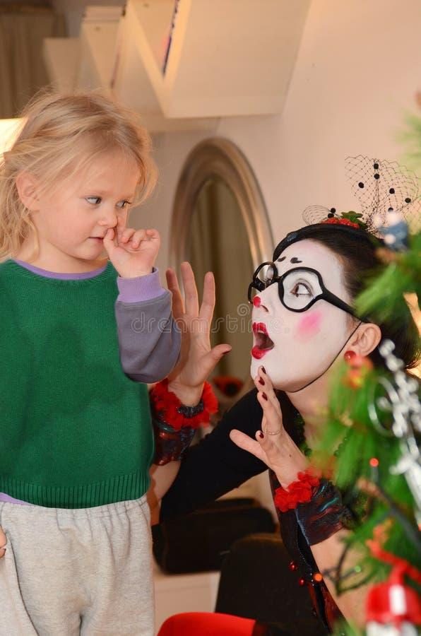 Девушк-пантомима развлекает маленький ребёнок стоковые фото