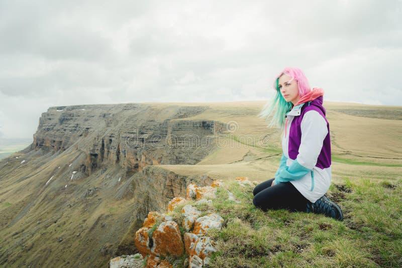 Девушк-путешественник с пестроткаными волосами сидит на краю скалы и смотрит к горизонту на предпосылке скалистого стоковые изображения rf