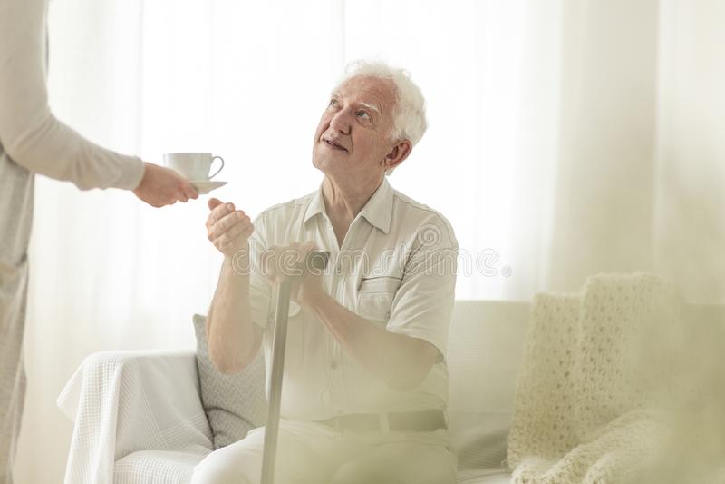 Дед держа тросточку и получая чай от его жены стоковые фотографии rf
